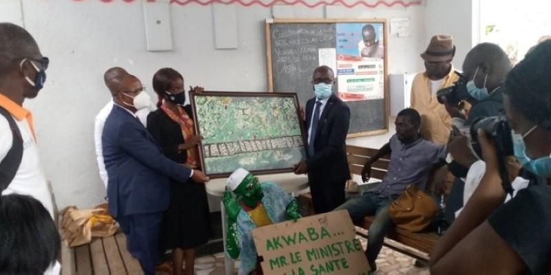 Le directeur de Cabinet du ministre de la santé, Dr Koffi Aka Charles (à droite du tableau), recevant un objet d'art réalisé par des usagers de la drogue remis de l'addiction. (Dr)