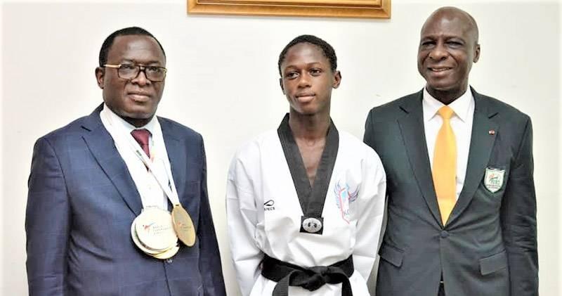 Le jeune taekwondo-in ivoirien, entre le ministre des Sports, à gauche, et le président de la Fitkd est une véritable graine de champion. (Photo : DR)