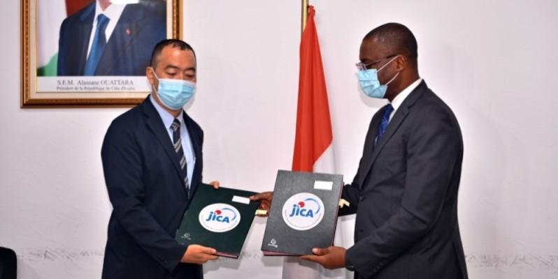 Échange de parapheurs entre le ministre Sidi Téimoko Touré et le Représentant résident adjoint de la Jica, Usui Yukichi.