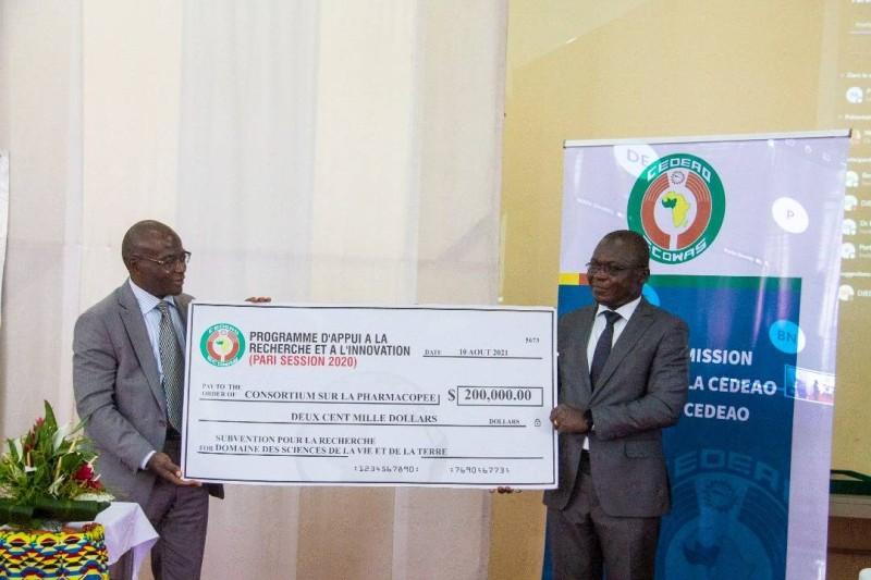 Le Directeur de cabinet du ministre de l'enseignement supérieur et de la recherche scientifique, Pr Arsène Kobéa remettant le chèque au Pr N'Guessan Jean David. (DR)