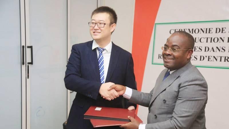 Échange de parapheurs entre le Pr Justin Koffi, directeur général de l'Arre et Xu Yang, représentant de l'entreprise Tbea en Côte d'Ivoire. (Photo: DR)