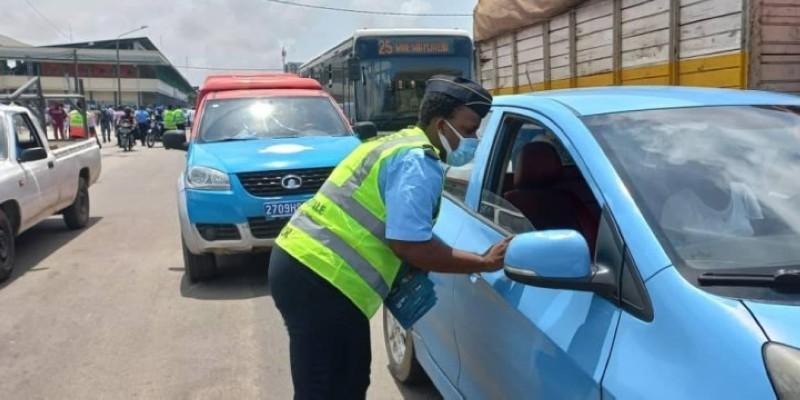 Un agent de police contrôle les pièces d'un véhicule au grand carrefour de Koumassi.