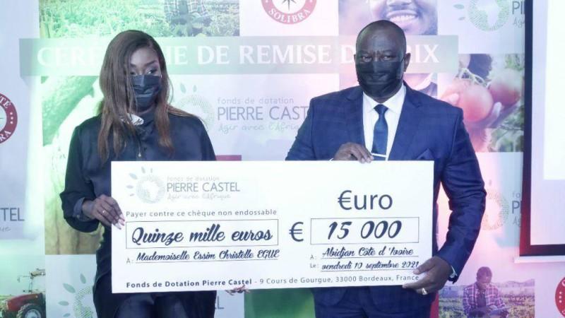 Mlle Christelle Essim Egue recevant son chèque des mains du ministre Adjoumani
