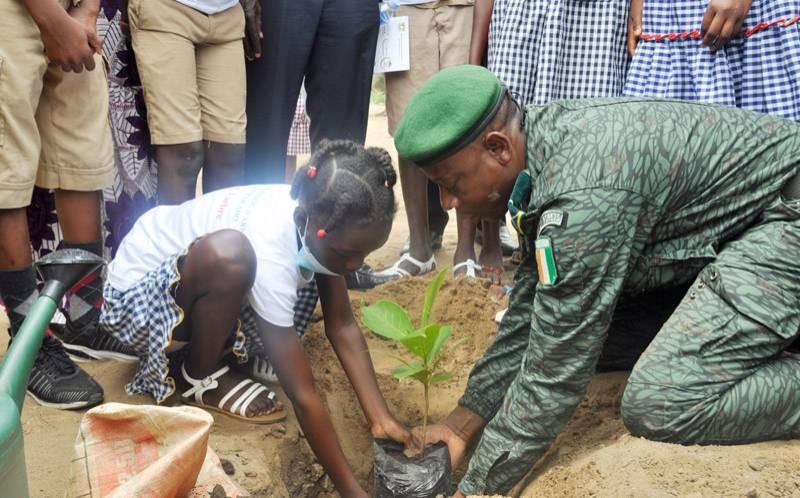 Un agent des Eaux et Forêts plantant un arbre avec une écolière. (DR)